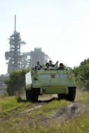 KENNEDY SPACE CENTER, FLA. -- Driven by Mission Specialist Daniel Tani, the M-113 armored personnel carrier moves through the underbrush near Launch Pad 39A. The M-113 is part of emergency exit procedures from Launch Pad 39A. Also in front is the trainer. In the rear are Mission Specialists Doug Wheelock, Scott Parazynski and Paolo Nespoli, who represents the European Space Agency. The training is part of terminal countdown demonstration test, or TCDT, activities the crew is undertaking at NASA's Kennedy Space Center. The TCDT also includes equipment familiarization and a simulated launch countdown. Mission STS-120, which will carry the Italian-built U.S. Node 2 to the International Space Station, is targeted for launch on Oct. 23. Photo credit: NASA/Kim Shiflett