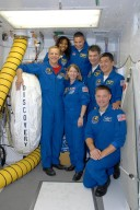 KENNEDY SPACE CENTER, FLA. -- Gathered in the white room on Launch Pad 39A, alongside space shuttle Discovery, the STS-120 crew pauses for a photo. Clockwise from the bottom are Commander Pamela Melroy, Mission Specialists Scott Parazynski and Stephanie Wilson, Pilot George Zamka, Mission Specialists Paolo Nespoli, Daniel Tani and Doug Wheelock (kneeling). Nespoli represents the European Space Agency. After the mission, Tani will remain aboard the International Space Station and return with the STS-122 crew, targeted to launch Dec. 6. The crew is at NASA's Kennedy Space Center for the pre-launch terminal countdown demonstration test, or TCDT. The TCDT provides astronauts and ground crews an opportunity to participate in various simulated countdown activities, including equipment familiarization and emergency training. The STS-120 mission will deliver the U.S. Node 2 module, named Harmony, aboard space shuttle Discovery to the International Space Station. Launch of Discovery on mission STS-120 is targeted for Oct. 23 at 11:38 a.m. EDT on a 14-day mission. Photo credit: NASA/Kim Shiflett