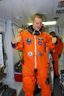 KENNEDY SPACE CENTER, FLA. -- In the white room on Launch Pad 39A, STS-120 Mission Specialist Scott Parazynski dons his parachute pack before entering space shuttle Discovery for a simulated launch countdown. The countdown is the culmination of the prelaunch terminal countdown demonstration test, or TCDT. His name patch reflects the nicknames the crew gave each other for the event. The TCDT at NASA's Kennedy Space Center provides astronauts and ground crews an opportunity to participate in various launch preparation activities, including equipment familiarization and emergency training. The STS-120 mission will deliver the U.S. Node 2 module, named Harmony, aboard space shuttle Discovery to the International Space Station. Discovery is targeted to launch on its 14-day mission at 11:38 a.m. EDT on Oct. 23. Photo credit: NASA/George Shelton
