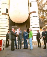 KENNEDY SPACE CENTER, FLA. -- Vice President George F. Bush, center, flanked by astronauts Robert L. Crippen on his right and John W. Young on his left, receives a model of the Space Shuttle from Dr. Alan M. Lovelace, acting administrator of the National Aeronautics and Space Administration. At far right is Mrs. Bush, who accompanied the vice president on his whirlwind tour of the Shuttle vehicle and launch facilities. In the background are the aft portions of the orbiter, external tank and solid rocket boosters. The Shuttle, America's first reusable space transportation system, is scheduled to make its maiden voyage into space no sooner than the week of April 7.