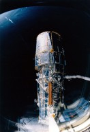 JOHNSON SPACE CENTER, HOUSTON, TEXAS -- View through overhead windows shows remote manipulator system (RMS) arm with telescope in grasp before procedures start to deploy solar array panels and antennae.