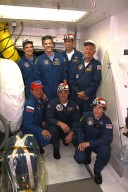 STS-86 crew members pose for a group photograph outside the hatch to the crew cabin of the Space Shuttle Atlantis at Launch Pad 39A. Kneeling in front, from left, are Mission Specialists Vladimir Georgievich Titov of the Russian Space Agency, David A. Wolf and Wendy B. Lawrence. Standing, from left, are Pilot Michael J. Bloomfield, Mission Specialist Scott E. Parazynski, Commander James D. Wetherbee, and Mission Specialist Jean-Loup J.M. Chretien of the French Space Agency, CNES. STS-86 will be the seventh docking of the Space Shuttle with the Russian Space Station Mir. During the docking, Wolf will transfer to the orbiting Russian station and become a member of the Mir 24 crew, replacing U.S. astronaut C. Michael Foale, who has been on the Mir since the last docking mission, STS-84, in May. Launch of Mission STS-86 aboard the Space Shuttle Atlantis is targeted for Sept. 25