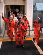 """The five STS-86 mission specialists wave to the crowd of press representatives, KSC employees and other well-wishers as they depart from the Operations and Checkout Building. The three U.S. mission specialists (and their nicknames for this flight) are, from left, """"too tall"""" Scott E. Parazynski, """"just right"""" David A. Wolf and """"too short"""" Wendy B. Lawrence. The two mission specialists representing foreign space agencies are Vladimir Georgievich Titov of the Russian Space Agency, in foreground at right, and Jean-Loup J.M. Chretien of the French Space Agency, CNES, in background at right. Commander James D. Wetherbee and Pilot Michael J. Bloomfield are out of the frame. STS-86 is slated to be the seventh docking of the Space Shuttle with the Russian Space Station Mir. Wolf is scheduled to transfer to the Mir 24 crew for an approximate four-month stay aboard the Russian space station. Parazynski and Lawrence were withdrawn from training for an extended stay aboard the Mir Parazynski because he was too tall to fit safely in a Russian Soyuz spacecraft, and Lawrence because she was too short to fit into a Russian spacewalk suit. The crew is en route to Launch Pad 39A, where the Space Shuttle Atlantis awaits liftoff on the planned 10-day mission"""