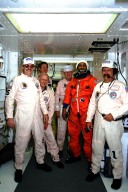 STS-87 Mission Specialist Winston Scott poses in his orange launch and entry spacesuit with NASA suit technicians at Launch Pad 39B during Terminal Countdown Demonstration Test (TCDT) activities. The crew of the STS-87 mission is scheduled for launch Nov. 19 aboard the Space Shuttle Columbia. Scott will be performing an extravehicular activity (EVA) spacewalk during the mission. The TCDT is held at KSC prior to each Space Shuttle flight providing the crew of each mission opportunities to participate in simulated countdown activities. The TCDT ends with a mock launch countdown culminating in a simulated main engine cut-off. The crew also spends time undergoing emergency egress training exercises at the pad and has an opportunity to view and inspect the payloads in the orbiter's payload bay