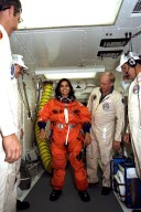 STS-87 Mission Specialist Kalpana Chawla, Ph.D., is assisted with her orange launch and entry spacesuit by NASA suit technicians at Launch Pad 39B during Terminal Countdown Demonstration Test (TCDT) activities. The crew of the STS-87 mission is scheduled for launch Nov. 19 aboard the Space Shuttle Columbia. The TCDT is held at KSC prior to each Space Shuttle flight providing the crew of each mission opportunities to participate in simulated countdown activities. The TCDT ends with a mock launch countdown culminating in a simulated main engine cut-off. The crew also spends time undergoing emergency egress training exercises at the pad and has an opportunity to view and inspect the payloads in the orbiter's payload bay