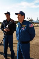As STS-87 Commander Kevin Kregel looks on, Payload Specialist Leonid Kadenyuk of the National Space Agency of Ukraine addresses members of the press and media at Kennedy Space Center's Shuttle Landing Facility after arriving for the final prelaunch activities leading up to the scheduled Nov. 19 liftoff. Other STS-87 crew members not pictured are Pilot Steven Lindsey; and Mission Specialists Kalpana Chawla, Ph.D.; Takao Doi, Ph.D., of the National Space Development Agency of Japan; and Winston Scott. STS-87 will be the fourth flight of the United States Microgravity Payload and the Spartan-201 deployable satellite