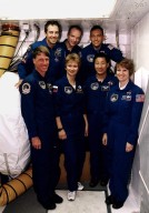 The STS-84 crew pose for a group photograph in front of the crew hatch of the Space Shuttle Atlantis at Launch Pad 39A. In the front row, from left, are Mission Specialists C. Michael Foale, Elena V. Kondakova of the Russian Space Agency, and Edward Tsang Lu; and Pilot Eileen Marie Collins. In the back row, from left, are Mission Specialist Jean-Francois Clervoy of the European Space Agency, Commander Charles J. Precourt and Mission Specialist Carlos I. Noriega. They are at KSC to participate in the Terminal Countdown Demonstration Test (TCDT), a dress rehearsal for launch. STS-84 will be the sixth docking of the Space Shuttle with the Russian Space Station Mir. After docking, Foale will transfer to the space station and become a member of the Mir 23 crew, replacing U.S. astronaut Jerry M. Linenger, who will return to Earth aboard Atlantis. Foale will live and work on Mir until mid-September when his replacement is expected to arrive on the STS-86 mission. STS-84 is targeted for a May 15 liftoff