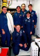 """KENNEDY SPACE CENTER, Fla. -- STS-88 crew members pose for a photograph in the white room, an environmental chamber, on launch pad 39A. In the front row are (left) Mission Commander Robert D. Cabana, Mission Specialists Jerry L. Ross (kneeling) and Nancy J. Currie; in the back row are Pilot Frederick W. """"Rick"""" Sturckow and Mission Specialists James H. Newman and Sergei Krikalev, a Russian cosmonaut. The crew are at KSC to participate in the Terminal Countdown Demonstration Test (TCDT), a dress rehearsal for launch. Mission STS-88 is targeted for launch on Dec. 3, 1998. It is the first U.S. flight for the assembly of the International Space Station and will carry the Unity connecting module"""