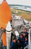 """KENNEDY SPACE CENTER, Fla. -- Flanked by a solid rocket booster and external tank at left, STS-88 crew members pose for a group photograph near the top of the Fixed Service Structure at Launch Pad 39A. They are (front to back) Mission Commander Robert D. Cabana, Mission Specialist Nancy J. Currie, Pilot Frederick W. """"Rick"""" Sturckow, Mission Specialists Jerry L. Ross, James H. Newman, and (at right) Sergei Krikalev, a Russian cosmonaut. The crew are at KSC to participate in the Terminal Countdown Demonstration Test (TCDT), a dress rehearsal for launch. Mission STS-88 is targeted for launch on Dec. 3, 1998. It is the first U.S. flight for the assembly of the International Space Station and will carry the Unity connecting module"""