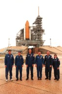"""KENNEDY SPACE CENTER, Fla. -- At launch pad 39A, the STS-88 crew pose for a photograph after Terminal Countdown Demonstration Test (TCDT) activities. From left, they are Mission Specialist Sergei Konstantinovich Krikalev, a Russian cosmonaut; Pilot Frederick W. """"Rick"""" Sturckow; Mission Specialist James H. Newman; Mission Commander Robert D. Cabana; Mission Specialist Jerry L. Ross; and Mission Specialist Nancy J. Currie. Mission STS-88 is targeted for launch on Dec. 3, 1998. It is the first U.S. flight for the assembly of the International Space Station and will carry the Unity connecting module"""