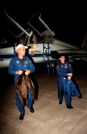 """STS-88 Pilot Frederick W. """"Rick"""" Sturckow (at left) and Mission Specialist Nancy J. Currie walk across the runway at the Shuttle Landing Facility after exiting the T-38 jet aircraft (in background) that brought them to KSC. They join the four other crew members, Commander Robert D. Cabana and Mission Specialists Jerry L. Ross, James H. Newman and Sergei Konstantinovich Krikalev, a Russian cosmonaut, for prelaunch preparations for mission STS-88 aboard Space Shuttle Endeavour. The scheduled time of launch is 3:56 a.m. EST on Dec. 3 from Launch Pad 39A. The mission is the first U.S. launch for the International Space Station. Endeavour carries the Unity connecting module which the crew will be mating with the Russian-built Zarya control module already in orbit. In addition to Unity, Endeavour will carry two small replacement electronics boxes for possible repairs to Zarya batteries. The mission is scheduled to last nearly 12 days"""