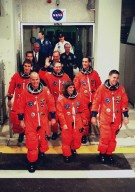 """The STS-88 crew leave the Operations and Checkout Building for their trip to Launch Pad 39A. In the front row (left to right) are Pilot Frederick W. """"Rick"""" Sturckow, Mission Specialist Nancy J. Currie and Commander Robert D. Cabana. Behind them (left to right) are Mission Specialist Sergei Konstantinovich Krikalev, a Russian cosmonaut, and Mission Specialists Jerry L. Ross and James H. Newman. STS-88 is expected to launch at 3:56 a.m. EST with the six-member crew aboard Space Shuttle Endeavour on Dec. 3. Endeavour carries the Unity connecting module, which the crew will be mating with the Russian-built Zarya control module already in orbit. In addition to Unity, two small replacement electronics boxes are on board for possible repairs to Zarya batteries. The mission is expected to last 11 days, 19 hours and 49 minutes, with landing at 10:17 p.m. EST on Dec. 14"""