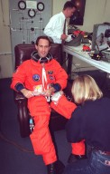 STS-88 Mission Specialist James H. Newman gets assistance from suit technician Terri McKinney while donning his orange launch and entry suit in the Operations and Checkout Building. STS-88 will be Newman?s third spaceflight. He also is scheduled to perform three spacewalks on the mission. He and the five other STS-88 crew members will depart shortly for Launch Pad 39A where the Space Shuttle Endeavour is poised for liftoff on the first U.S. mission dedicated to the assembly of the International Space Station