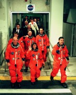 "Wearing their orange launch and entry suits, STS-88 crew members leave the Operations and Checkout Building en route to Launch Pad 39A, where the Space Shuttle Endeavour is poised for liftoff of the first U.S. launch dedicated to the assembly of the International Space Station. In front row, from left, are Pilot Frederick W. ""Rick"" Sturckow, Mission Specialist Nancy J. Currie and Commander Robert D. Cabana. In back row, from left, are Mission Specialists Sergei Konstantinovich Krikalev, a Russian cosmonaut; Jerry L. Ross and James H. Newman. Liftoff is targeted for 3:35 a.m. EST on Dec. 4"