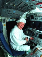 Ohio Senator John Glenn enjoys a tour of the flight deck in the orbiter Columbia at the Orbiter Processing Facility 3 at Kennedy Space Center. Senator Glenn arrived at KSC on Jan. 20 to tour KSC operational areas and to view the launch of STS-89 later this week. Glenn, who made history in 1962 as the first American to orbit the Earth, completing three orbits in a five-hour flight aboard Friendship 7, will fly his second space mission aboard Space Shuttle Discovery this October. Glenn is retiring from the Senate at the end of this year and will be a payload specialist aboard STS-95