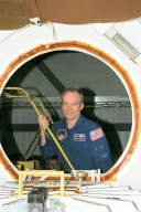 STS-91 Commander Charles Precourt peers through an airlock like the one that will be aboard the orbiter Discovery when it docks with the Russian Space Station Mir on the ninth and final scheduled Mir docking in late May/early June. Precourt is in KSC's Orbiter Processing Facility Bay 2 for the STS-91 Crew Equipment Interface Test, or CEIT, during which the crew have an opportunity to get a hands-on look at the payloads with which they will be working on-orbit. The STS-91 crew are scheduled to launch aboard the Shuttle Discovery from KSC's Launch Pad 39A on May 28 at 8:05 EDT