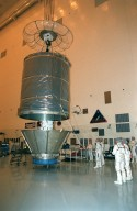 The cover is removed from the Stardust spacecraft in the Payload Hazardous Servicing Facility prior to a media presentation. Stardust is targeted for launch on Feb. 6 aboard a Boeing Delta II rocket from Launch Pad 17-A, Cape Canaveral Air Station. The spacecraft is destined for a close encounter with the comet Wild 2 in January 2004. Using a silicon-based substance called aerogel, Stardust will capture comet particles flying off the nucleus of the comet. The spacecraft also will bring back samples of interstellar dust. These materials consist of ancient pre-solar interstellar grains and other remnants left over from the formation of the solar system. Scientists expect their analysis to provide important insights into the evolution of the sun and planets and possibly into the origin of life itself. The collected samples will return to Earth in a sample return capsule (the white-topped, blunt-nosed cone seen on the top of the spacecraft) to be jettisoned as Stardust swings by Earth in January 2006