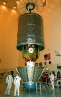 In the Payload Hazardous Servicing Facility, workers guide a protective canister as it is lowered over the Stardust spacecraft. Once it is enclosed, Stardust will be moved to Launch Pad 17-A, Cape Canaveral Air Station, for launch preparations. Stardust is targeted for liftoff on Feb. 6 aboard a Boeing Delta II rocket for a close encounter with the comet Wild 2 in January 2004. Using a silicon-based substance called aerogel, Stardust will capture comet particles flying off the nucleus of the comet. The spacecraft also will bring back samples of interstellar dust. These materials consist of ancient pre-solar interstellar grains and other remnants left over from the formation of the solar system. Scientists expect their analysis to provide important insights into the evolution of the sun and planets and possibly into the origin of life itself. The collected samples will return to Earth in a sample return capsule to be jettisoned as Stardust swings by Earth in January 2006