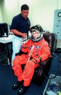 In the Operations and Checkout Building, STS-96 Pilot Rick D. Husband waves while being checked by a suit technician after donning his launch and entry suit during final launch preparations. STS-96 is a 10-day logistics and resupply mission for the International Space Station, carrying about 4,000 pounds of supplies, to be stored aboard the station for use by future crews, including laptop computers, cameras, tools, spare parts, and clothing. The mission also includes such payloads as a Russian crane, the Strela; a U.S.-built crane; the Spacehab Oceaneering Space System Box (SHOSS), a logistics items carrier; and STARSHINE, a student-involved experiment. It will include a space walk to attach the cranes to the outside of the ISS for use in future construction.. Space Shuttle Discovery is due to launch today at 6:49 a.m. EDT. Landing is expected at the SLF on June 6 about 1:58 a.m. EDT