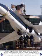 """Workers carefully align a mounting bracket attached to an F/A-18 Hornet aircraft with the top of a pedestal in front of the municipal baseball stadium in the city of Lancaster, California. The Blue-and-white twin-jet aircraft, formerly flown as a safety chase and support aircraft by NASA's Dryden Flight Research Center, Edwards, California, was loaned to the city for display following its recent retirement. Known as """"The Hangar,"""" the stadium is the home field of the Lancaster Jethawks, a Class-A farm team of the Seattle Mariners."""