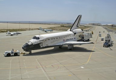 Shuttle Discovery, with recovery Vehicles, is to the Taxiway