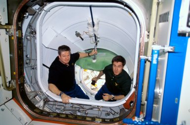 Shepherd and Krikalev in PMA preparing for hatch opening for STS-102