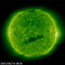 The main noteworthy feature on the Sun this past week is the one, dark, coronal hole that we watched as it rotated to the Sun's center over three days (June 17-19, 2007). Anyone who inspects the movie carefully will note that there were no looping arcs, no flares or solar storms, no filaments, and no bright active regions. Yes, the Sun remained largely featureless except for the coronal hole, and even that hole is not particularly large as these things go. We should note too that the north and the south poles of the Sun also have polar coronal holes that are becoming more distinct as we approach solar minimum. Coronal holes are cooler, darker areas when observed in extreme ultraviolet light as the Sun is here. Since coronal holes are 'open' magnetically, strong solar wind gusts can escape from them and carry solar particles out to our magnetosphere and beyond. The Sun is near its minimum period of activity in its 11-year solar cycle and it shows it in this way.