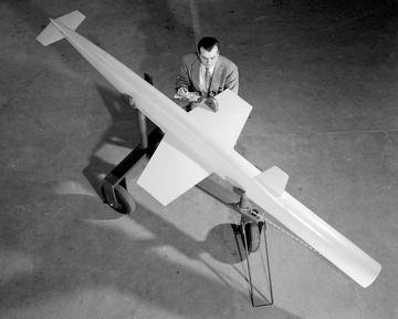 AERODYNAMICS ENGINEER WITH RAM JET NO. 2 SCALE MODEL FOR USE IN RECRUITING BROCHURE