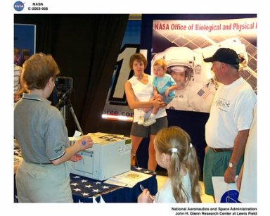 NASA GLENN RESEARCH CENTER EMPLOYEE ENJOYS CAPTURING NASA'S NEXT GENERATION ASTRONAUT PORTRAITS AT PICTURE YOURSELF IN SPACE BOOTH AT THE WRIGHT PATTERSON AIR FORCE BASE OPEN HOUSE - AIR POWER 2003, MAY 10-11, 2003