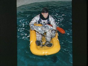 Astronaut Walter Schirra in life raft in pool at air base during training