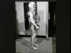 Astronaut Alan Shepard in pressure suit with body parachute