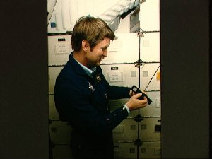 STS 51-F Mission specialist Anthony England shows off Panasonic camera