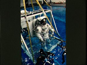 Astronaut Dunbar, in EMU, is lowered into JSC's WETF pool for EVA simulation