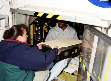 STS-99 workers move new Master Events Controller into aft compartment