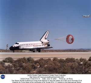 The Space Shuttle Endeavour's drag chute deploys to slow the orbiter as it rolls out on Runway 22 at