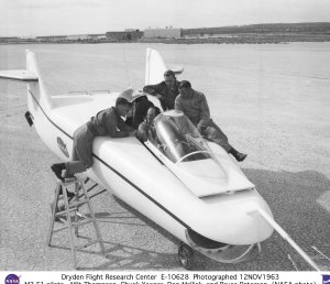 M2-F1 on lakebed with pilots Milt Thompson, Chuck Yeager, Don Mallick, and Bruce Peterson