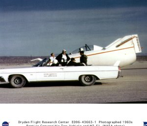 M2-F1 on lakebed with Pontiac convertible tow vehicle