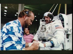 Astronaut Joseph Tanner is assisted into his EMU during training