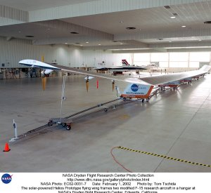 The solar-powered Helios Prototype flying wing frames two modified F-15 research aircraft in a hanga