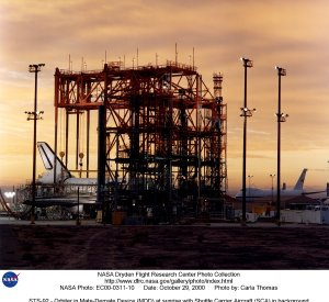 STS-92 - Orbiter in Mate-Demate Device (MDD) at sunrise with Shuttle Carrier Aircraft (SCA) in backg