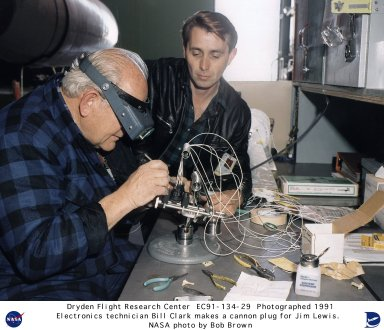 Electronics technician Bill Clark assembling a cannon plug with the help of Jim Lewis