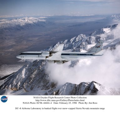 DC-8 Airborne Laboratory in banked flight over snow-capped Sierra Nevada mountain range