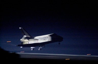 """KENNEDY SPACE CENTER, Fla. -- Space Shuttle Atlantis glows from the landing lights as it nears touchdown on KSC?s Shuttle Landing Facility Runway 15 to complete the 9-day, 20-hour, 9-minute-long STS-101 mission. At the controls are Commander James D. Halsell Jr. and Pilot Scott """"Doc"""" Horowitz. Also onboard the orbiter are Mission Specialists Mary Ellen Weber, James S. Voss, Jeffrey N. Williams, Susan J. Helms and Yury Usachev of Russia. The crew is returning from the third flight to the International Space Station. This was the 98th flight in the Space Shuttle program and the 21st for Atlantis, also marking the 51st landing at KSC, the 22nd consecutive landing at KSC, and the 29th in the last 30 Shuttle flights. Main gear touchdown was at 2:20:17 a.m. EDT, landing on orbit 155 of the mission. Nose gear touchdown was at 2:20:30 a.m. EDT, and wheel stop at 2:21:19 a.m. EDT"""