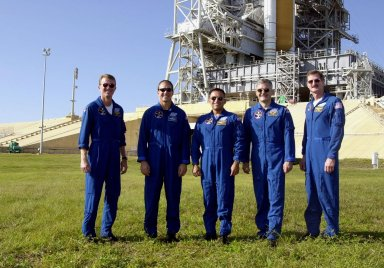 KENNEDY SPACE CENTER, Fla. -- The STS-97 crew pose for photographers at the base of Launch Pad 39B. They are, left to right, Commander Brent Jett, Pilot Mike Bloomfield and Mission Specialists Carlos Noriega, Marc Garneau and Joe Tanner. Garneau is with the Canadian Space Agency. The crew is at KSC to take part in Terminal Countdown Demonstration Test activities that include emergency egress training, familiarization with the payload, and a simulated launch countdown. Visible in the background are the solid rocket booster and external tank on Space Shuttle Endeavour. Mission STS-97is the sixth construction flight to the International Space Station. Its payload includes the P6 Integrated Truss Structure and a photovoltaic (PV) module, with giant solar arrays that will provide power to the Station. The mission includes two spacewalks to complete the solar array connections. STS-97 is scheduled to launch Nov. 30 at about 10:05 p.m. EST