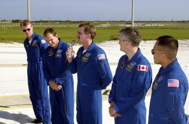 KENNEDY SPACE CENTER, Fla. -- From the slidewire landing zone at Launch Pad 39B, STS-97 Mission Specialist Joe Tanner (center, with microphone) speaks to the press about his extravehicular activity (EVA) during the mission. With him are the rest of the crew, Commander Brent Jett and Pilot Mike Bloomfield on the left and Mission Specialists Marc Garneau and Carlos Noriega on the right. The crew is at KSC to take part in Terminal Countdown Demonstration Test activities that include emergency egress training, familiarization with the payload, and a simulated launch countdown. Visible in the background are the solid rocket booster and external tank on Space Shuttle Endeavour. Mission STS-97is the sixth construction flight to the International Space Station. Its payload includes the P6 Integrated Truss Structure and a photovoltaic (PV) module, with giant solar arrays that will provide power to the Station. The mission includes two spacewalks to complete the solar array connections. STS-97 is scheduled to launch Nov. 30 at about 10:05 p.m. EST