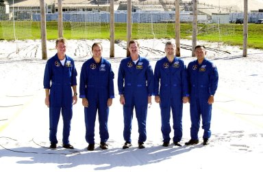 KENNEDY SPACE CENTER, Fla. -- The STS-97 crew poses for another photo after meeting with the media at the slidewire landing zone. They are, left to right, Commander Brent Jett, Pilot Mike Bloomfield and Mission Specialists Joe Tanner, Marc Garneau and Carlos Noriega. Garneau is with the Canadian Space Agency. The nets suspended behind them are a braking system catch net for the slidewire baskets that provide emergency exit from the orbiter and Fixed Service Structure. The crew is at KSC to take part in Terminal Countdown Demonstration Test activities that include emergency egress training, familiarization with the payload, and a simulated launch countdown. Visible in the background are the solid rocket booster and external tank on Space Shuttle Endeavour. Mission STS-97is the sixth construction flight to the International Space Station. Its payload includes the P6 Integrated Truss Structure and a photovoltaic (PV) module, with giant solar arrays that will provide power to the Station. The mission includes two spacewalks to complete the solar array connections. STS-97 is scheduled to launch Nov. 30 at 10:05 p.m. EST