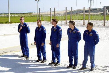 KENNEDY SPACE CENTER, Fla. -- Standing in the slidewire landing zone at Launch Pad 39B, the STS-97 crew respond to questions from the media. They are, left to right, Commander Brent Jett, Pilot Mike Bloomfield and Mission Specialists Joe Tanner, Marc Garneau and Carlos Noriega. Garneau is with the Canadian Space Agency. The nets suspended behind them are a braking system catch net for the slidewire baskets that provide emergency exit from the orbiter and Fixed Service Structure. The crew is at KSC to take part in Terminal Countdown Demonstration Test activities that include emergency egress training, familiarization with the payload, and a simulated launch countdown. Visible in the background are the solid rocket booster and external tank on Space Shuttle Endeavour. Mission STS-97is the sixth construction flight to the International Space Station. Its payload includes the P6 Integrated Truss Structure and a photovoltaic (PV) module, with giant solar arrays that will provide power to the Station. The mission includes two spacewalks to complete the solar array connections. STS-97 is scheduled to launch Nov. 30 at about 10:05 p.m. EST