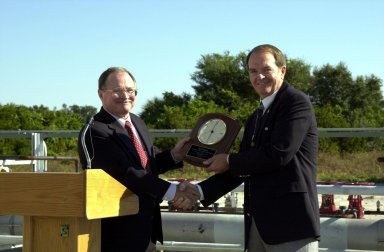 Jerry Jorgensen, pipeline project manager, Space Gateway Support (SGS) presents an award of appreciation to H.T. Everett, KSC Propellants manager, at the commissioning of a new high-pressure helium pipeline at Kennedy Space Center. The pipeline will service launch needs at the new Delta IV Complex 37 at Cape Canaveral Air Force Station. The nine-mile-long buried pipeline will also serve as a backup helium resource for Shuttle launches. Nearly one launch?s worth of helium will be available in the pipeline to support a Shuttle pad in an emergency. The line originates at the Helium Facility on KSC and terminates in a meter station at the perimeter of the Delta IV launch pad. Others at the ceremony were Center Director Roy Bridges;); Col. Samuel Dick, representative of the 45th Space Wing; Ramon Lugo, acting executive director, JPMO; David Herst, director, Delta IV Launch Sites; Pierre Dufour, president and CEO, Air Liquide America Corporation; and Michael Butchko, president, SGS