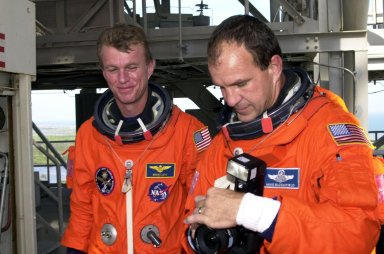 On the Fixed Service Structure of Launch Pad 39B, STS-97 Commander Brent Jett (left) watches Pilot Mike Bloomfield (right) adjust a camera. They are taking part in a simulated launch countdown, part of Terminal Countdown Demonstration Test activities that also include emergency egress training and familiarization with the payload. The other crew members are Mission Specialists Joe Tanner, Carlos Noriega and Canadian astronaut Marc Garneau. Mission STS-97 is the sixth construction flight to the International Space Station. Its payload includes the P6 Integrated Truss Structure and a photovoltaic (PV) module, with giant solar arrays that will provide power to the Station. The mission includes two spacewalks to complete the solar array connections. STS-97 is scheduled to launch Nov. 30 at 10:05 p.m. EST