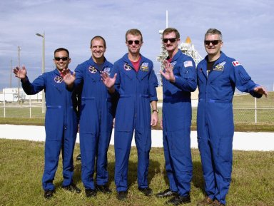 The STS-97 crew members wave for the camera as they gather outside Launch Pad 39B. Standing left to right are Mission Specialist Carlos Noriega, Pilot Michael Bloomfield, Commander Brent Jett and Mission Specialists Joseph Tanner and Marc Garneau, who is with the Canadian Space Agency. The mission to the International Space Station carries the P6 Integrated Truss Segment containing solar arrays and batteries that will be temporarily installed to the Unity connecting module by the Z1 truss, recently delivered to and installed on the Station on mission STS-92. The two solar arrays are each more than 100 feet long. They will capture energy from the sun and convert it to power for the Station. Two spacewalks will be required to install the solar array connections. STS-97 is scheduled to launch Nov. 30 at about 10:06 p.m. EST
